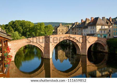 Reflection of the bridge and Old Palace of Espalion in Aubrac, France - stock photo