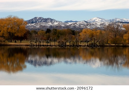 Reflection of the fall color, trees and mountains in the water. Focus is on horizon line. - stock photo