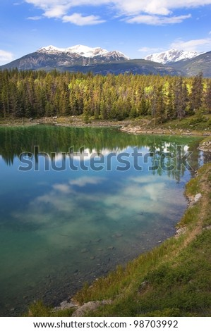 reflection of the forest and the sky in the emerald lake. Banff Alberta, Canada - stock photo