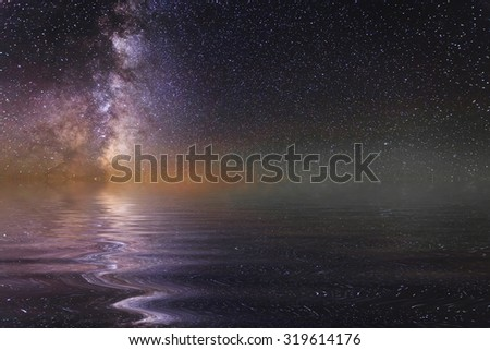Reflection of the night sky and stars in the water. - stock photo