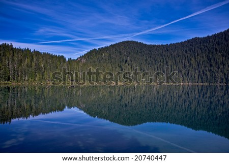 Reflection of the sky and jet trails in a still mountain lake - stock photo