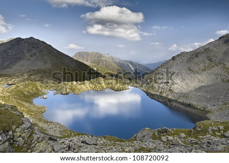 Reflection of the sky in a lake at high altitude. Crow Lake, Dolomites - stock photo