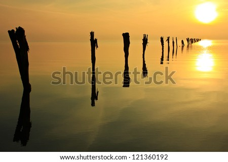 Reflection of the sun with silhouetted fence posts in the Great Salt Lake, Utah, USA. - stock photo