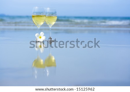 Reflection of two glasses of white wine on tropical beach