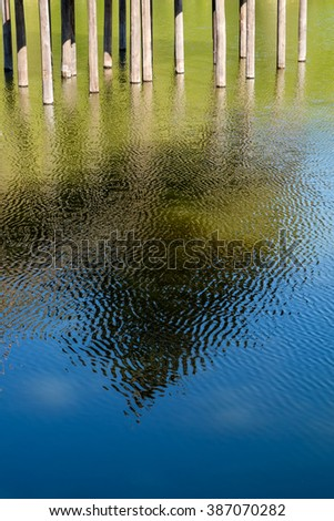 Reflection of wooden poles in the water - stock photo
