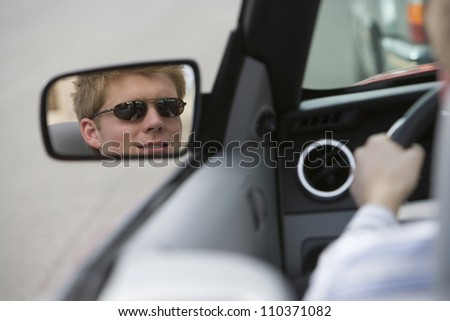 Reflection of young man in side view mirror of car