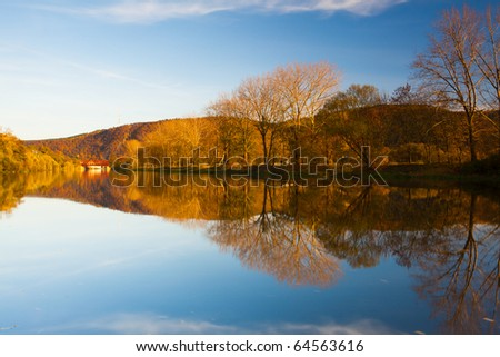 Reflection on the river in autumn at sunrise