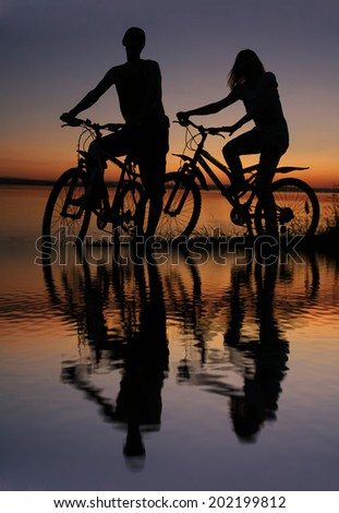 Reflection on the water Image of silhouette sporty couple on bicycles outdoors against water in sea texture blue and yellow sunset sky. Copy space for inscription Reflection on the ocean - stock photo