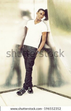 Reflection. Wearing a white V neck T shirt, pants, leather shoes, wristwatch, hands in pocket,  a young black handsome man is leaning back against  metal mirror walls, lost in thought. - stock photo
