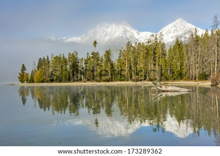 Reflections and fog in a mountain landscape - stock photo