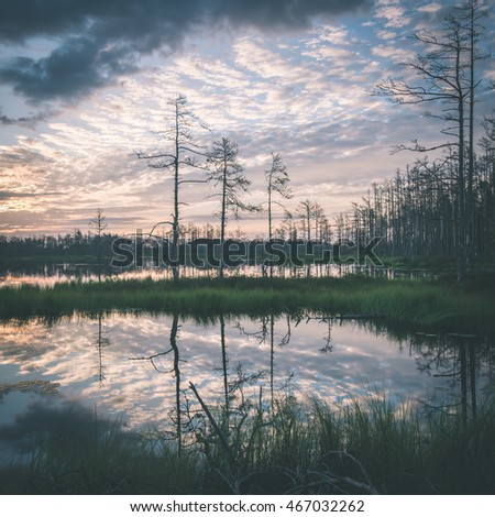 reflections in the lake water at sunrise with clouds and dramatic colors - vintage film effect