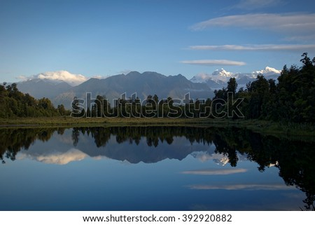Reflections in the late evening of the Mount Cook and Mount Tasman mountains on the Lake Matheson, New Zealand  - stock photo