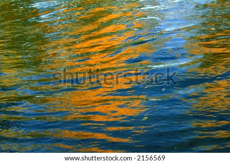 Reflections of bold autumn colors on blue waters create an impressionistic abstract - stock photo