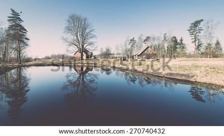 reflections of country house in the pond with trees and blue sky - retro vintage film effect