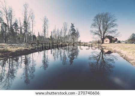 reflections of country house in the pond with trees and blue sky - retro vintage film effect - stock photo