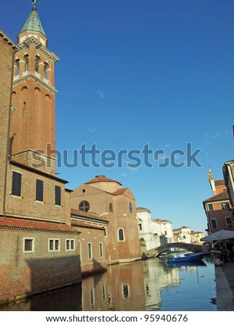 reflections of the medieval church in the Canal in Chioggia near Venice