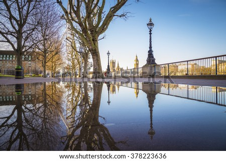Reflections of the The Big Ben and Houses of Parliament taken from South Bank of River Thames early in the morning with trees and clear blue sky - London, UK - stock photo