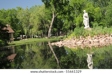 Reflections-Old statue in pond Wamego,Kansas This is correct spelling - stock photo