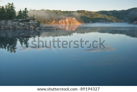 reflections on george lake looking to the forested ridges - stock photo