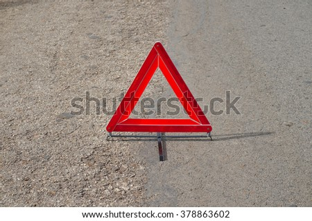 Reflective car warning triangle on the road. Driving and safety themes - stock photo