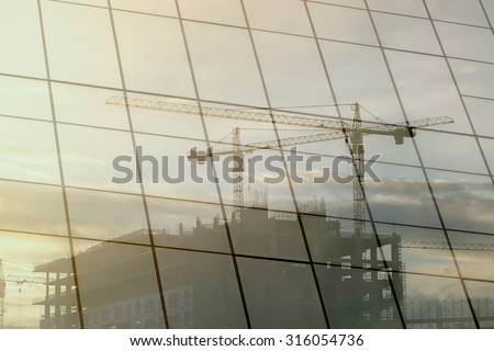Reflective glass building of construction crane - Construction e - stock photo
