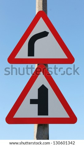 Reflective metallic road sign, warning of a right bend and left junction. Metaphor for a change of direction and conflict 'from left field' - stock photo