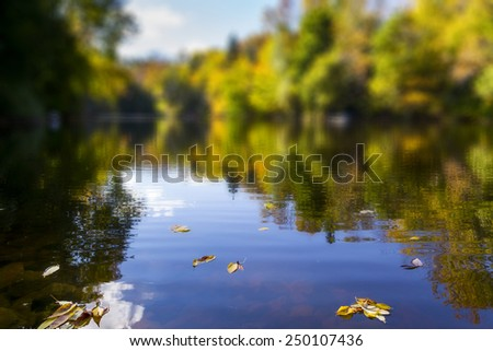 Reflective Still Pond in Autumn with a Blurry Filter Effect - stock photo