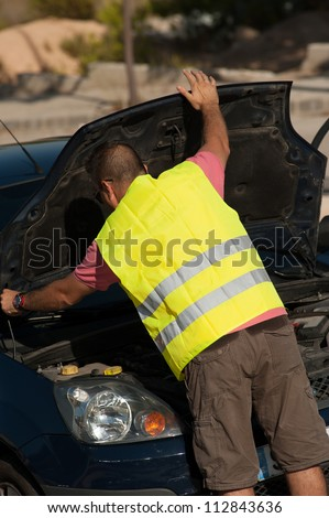 Reflective vest on and opening the car bonnet - stock photo