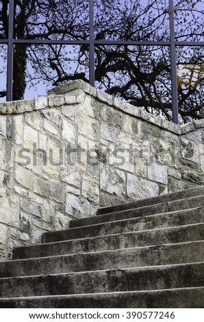 Reflective window panes above stone wall and concrete stairs from street level to the River Walk in downtown San Antonio, Texas, in February, for urban, travel, or architectural themes - stock photo