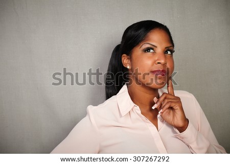 Reflective woman of afro-american ethnicity contemplating with hand on chin