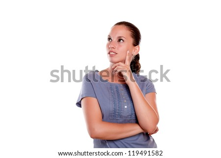Reflective young female looking to her right up on blue blouse on isolated background - copyspace - stock photo
