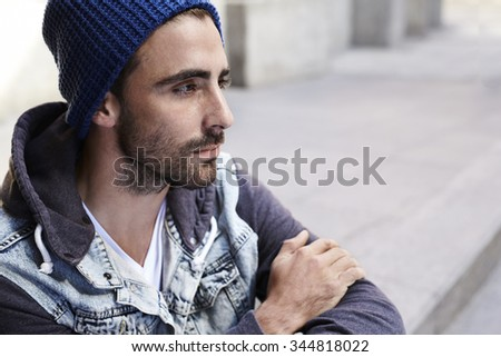 Reflective young man looking away - stock photo