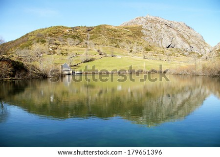 Refletion in a reservoir of water in Valle del Lago, Somiedo, Asturias, Spain. - stock photo