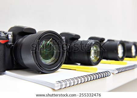 Reflex digital cameras with notepad in the classroom photo-school close-up - stock photo