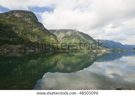 Reflexion of mountains in a water smooth surface of lake Sandvevatnet. Odda, Hordaland, Norway
