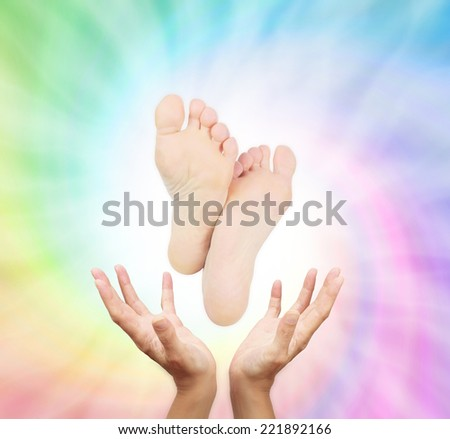 Reflexologist's outstretched hands with a pair of feet floating above on a spiraling healing rainbow colored energy background - stock photo