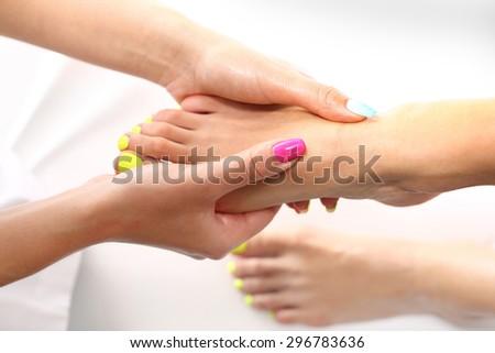Reflexology foot massage. Beautician massaging woman's foot, acupressure treatment - stock photo