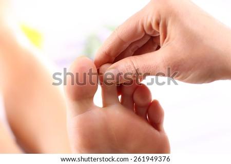Reflexology zones foot massage.Masseuse massaging woman's foot. - stock photo