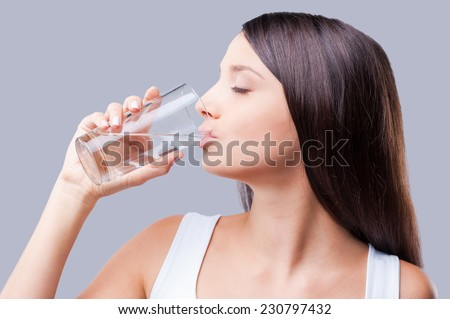 Refreshing and useful.  Beautiful young woman drinking water while standing against grey background  - stock photo