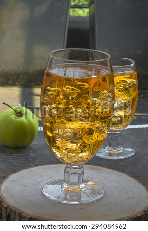 Refreshing apple cider with ice cubes and apples on wooden table - stock photo