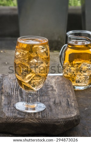 Refreshing apple cider with ice cubes on wooden table - stock photo