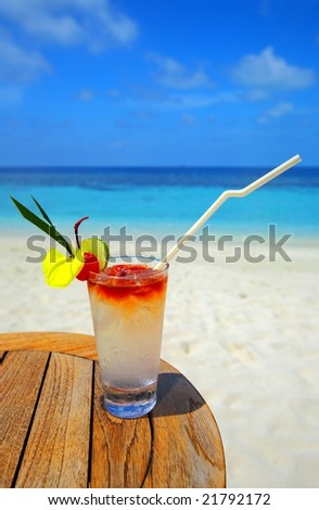 Refreshing cocktail on a beach table - stock photo