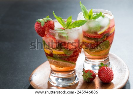 refreshing cocktail with strawberry and citrus in glasses, horizontal, close-up - stock photo
