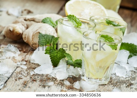refreshing cold drink with ginger, lemon, ice and mint, selective focus - stock photo