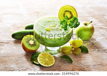 Refreshing green detox smoothie with cucumber, apple, grapes and kiwi on wooden background, healthy eating, vitamins