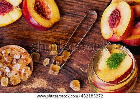 Refreshing iced green tea with peaches and mint, served in a glass with ice cubes and brown sugar on rustic wooden board, selective focus - stock photo