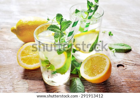 Refreshing iced mint tea with lemon and ice cubes, a drink for hot summer days selective focus, toned image - stock photo
