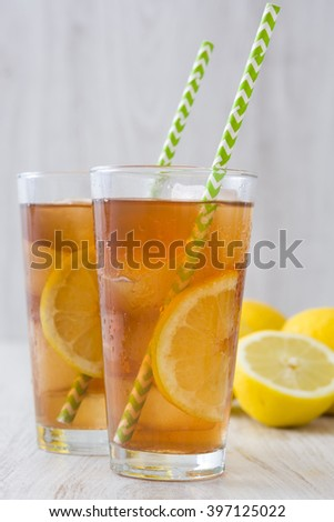 refreshing iced tea with lemon on white wood