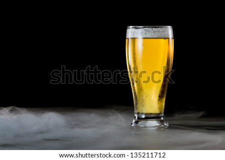 refreshing light beer in a cold glass served on a dark bar with fog - stock photo
