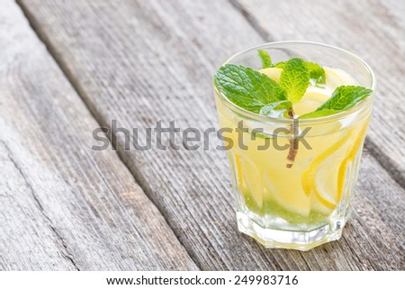 refreshing mint lemonade in glass on a wooden background, close-up - stock photo